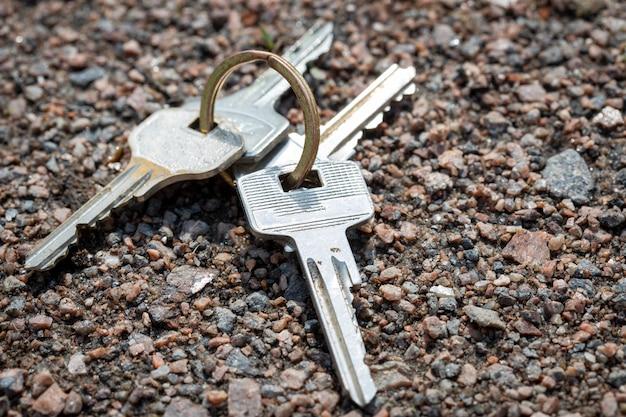 Le chiavi giacciono sulla sabbia in natura. perdita di effetti personali. foto di alta qualità