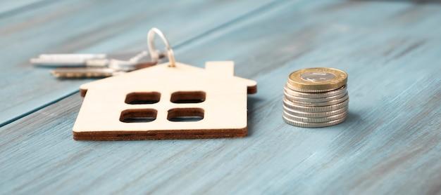 Chiavi e casa in miniatura. concetto di bene immobile. chiavi e monete