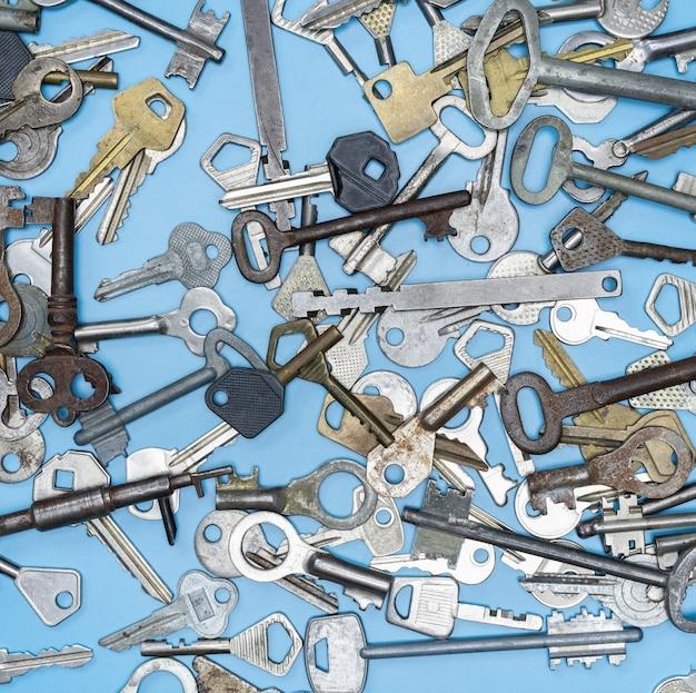 Chiavi impostate su sfondo blu. chiavi della serratura della porta e casseforti per la sicurezza della proprietà e la protezione della casa. diversi tipi di chiavi antiche e nuove.