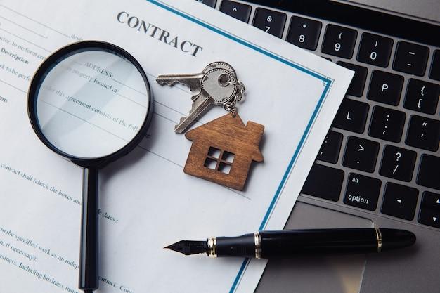 Chiavi con casa in legno, lente d'ingrandimento e contratto su un laptop. concetto di affitto, ricerca, acquisto di immobili