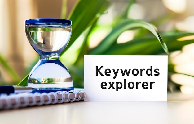 Esplora parole chiave - testo del concetto di business su un taccuino bianco e un orologio a clessidra, foglie verdi di fiori
