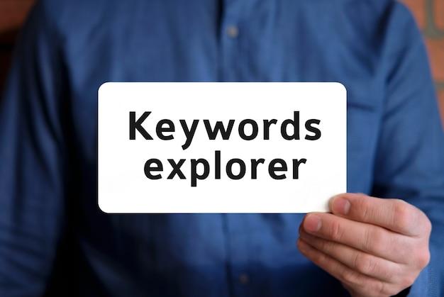 Parole chiave esploratore - testo su un cartello bianco nella mano di un uomo con una camicia blu