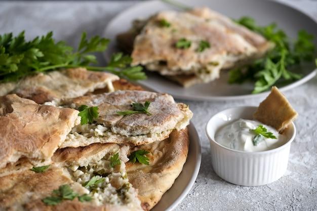 Khachapuri con ricotta e panna acida con prezzemolo verde sul piatto