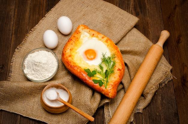 Khachapuri con le uova su tela di sacco, sale, farina e uova sulla tavola di legno
