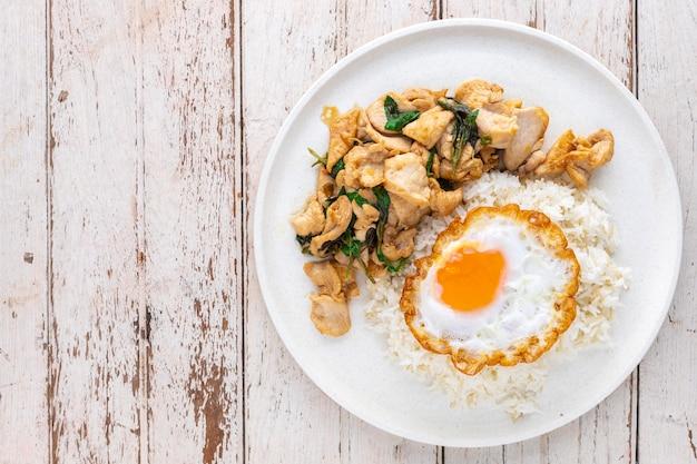Khao pad ka prao gai kai dao, cibo tailandese, riso in streaming condito con basilico mescolare pollo fritto e uovo fritto in piatto di ceramica bianca su sfondo bianco vecchio legno texture con spazio copia, vista dall'alto