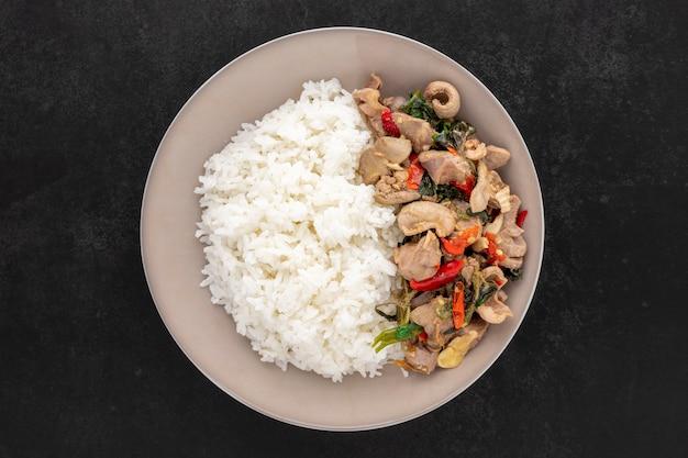 Khao pad ka prao kruang nai gai, cibo tailandese, riso in streaming con frattaglie di pollo fritte mescolate al basilico, carni varie, carni di carne o organi su sfondo scuro, vista dall'alto