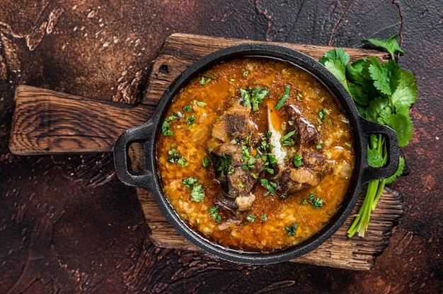 Zuppa di kharcho con carne di agnello, riso, pomodori, carote, peperoni, noci e spezie. sfondo scuro. vista dall'alto.