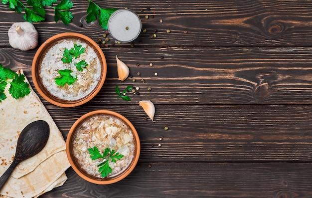 Khash in una ciotola. piatto di zuppa tradizionale armeno, brodo di carne, servito con verdure, aglio e lavash di pane nazionale. piatti di argilla, tavolo in legno con copia spazio