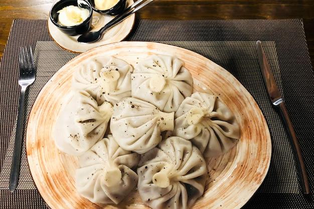 Khinkali cucinato su un piatto di ceramica con salsa su un tavolo di legno in un ristorante