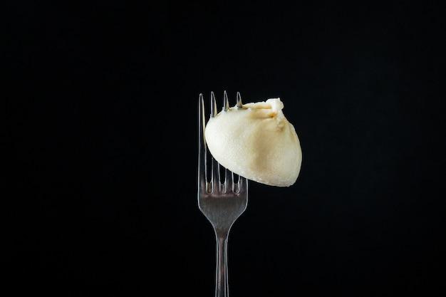 Khinkali con gnocchi di salsa ripieni su una forchetta