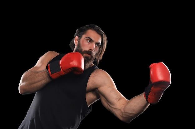 Uomo di kickboxer che combatte contro lo sfondo nero. concetto di sport.