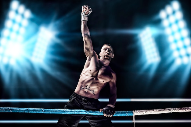 Kickboxer in posa sul ring. l'atleta ha scalato le corde e ha preso una posizione vittoriosa sullo sfondo dei riflettori.