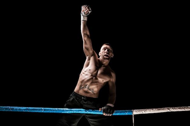 Kickboxer in posa sul ring. l'atleta si è arrampicato sulle corde e ha preso una posa vincente. il concetto di mma, wrestling, muay thai. tecnica mista