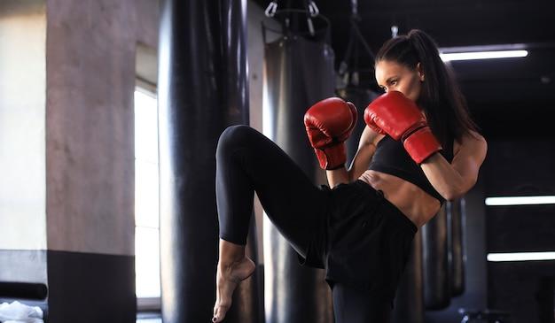 Kickboxing donna in activewear e guanti da kickboxing rossi su sfondo nero eseguendo un calcio di arti marziali. esercizio sportivo, allenamento fitness.