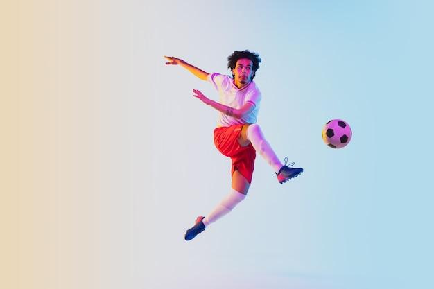 Calciare in salto in corsa giocatore di calcio o di calcio su sfondo sfumato in luce al neon