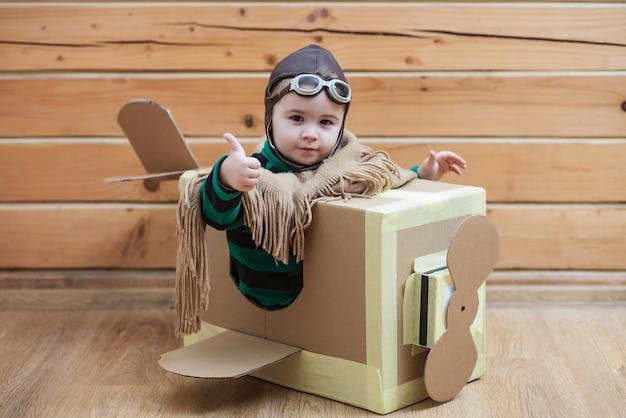 Pilota del bambino del bambino che si diverte in aeroplano di cartone sull'infanzia e sulla felicità del muro bianco