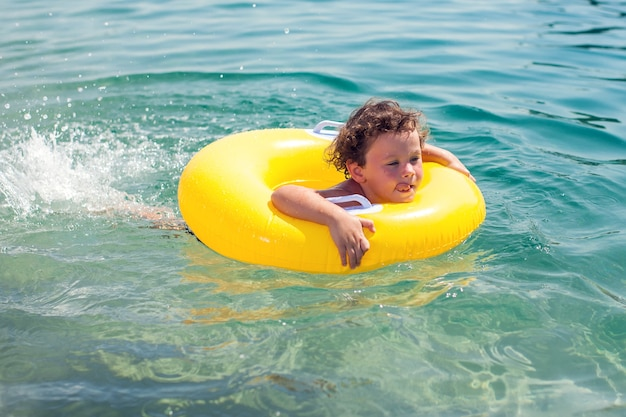 Kid sulla spiaggia con cerchio di nuoto. ragazzo che nuota nel mare. bambini e concetto di vacanza
