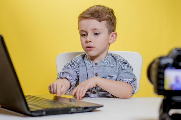 Kid blogger riprese video sulla fotocamera che lavora con il computer portatile.