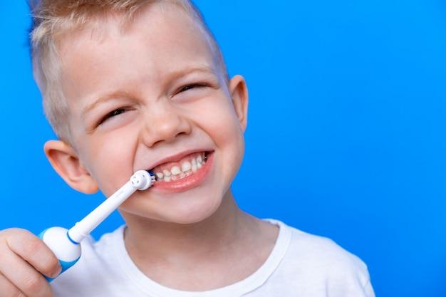 Ragazzo del bambino lavarsi i denti con spazzolino elettrico su blu