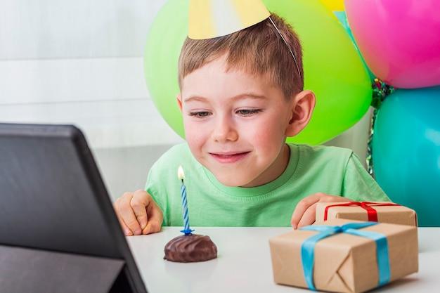 Il ragazzo del bambino festeggia il compleanno online con un amico o i nonni in videochiamata