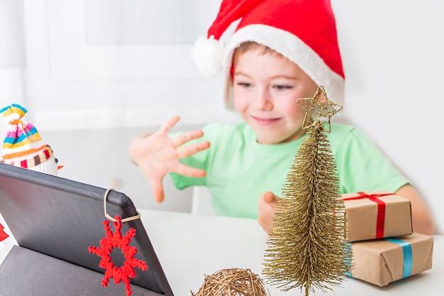 Kid boy festeggia il natale online con amici o nonni in videochiamata su tablet
