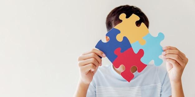 Mani del ragazzo del bambino che tengono il puzzle, il concetto di salute mentale, la giornata mondiale della consapevolezza dell'autismo
