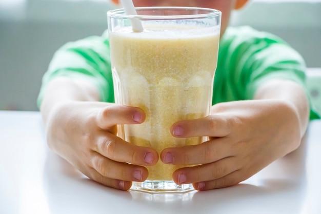 Ragazzo del bambino che tiene un bicchiere di frullato con arancia, banana, cagliata. bevanda vegetariana biologica fresca. alimenti per bambini di milkshake giallo o cocktail