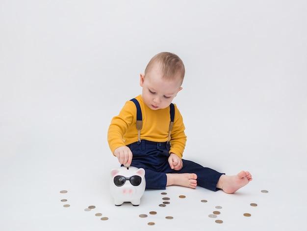Il bambino gioca con il salvadanaio e denaro. imparare un account
