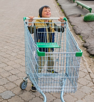 Ragazzo del bambino che spinge il carrello vuoto al parcheggio