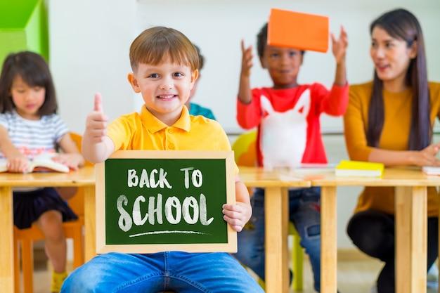 Pollici del ragazzo del bambino su e che tengono lavagna con di nuovo alla parola della scuola con gli amici di diversità