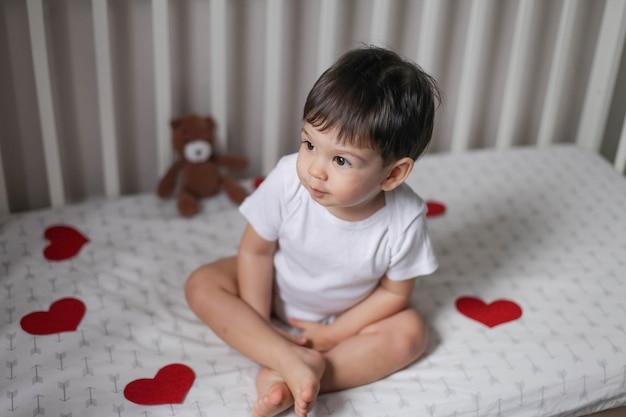 Ragazzo del bambino con i capelli scuri in un corpo bianco seduto sul letto bianco sotto ghirlande di cuori rossi il giorno di san valentino e sorridente.