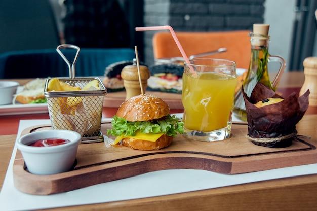 Colazione per bambini con mini hamburger, succo di frutta, torta e patate