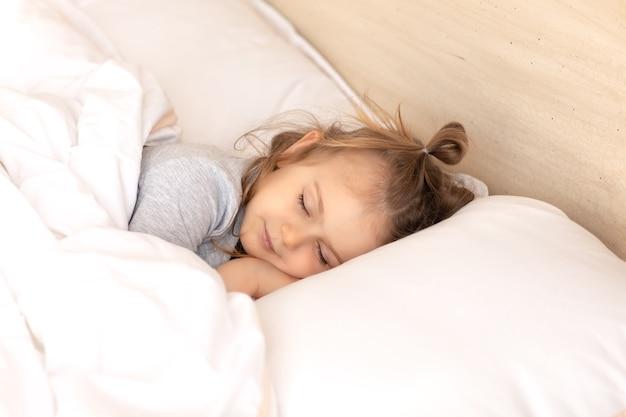 Il bambino ha gli occhi chiusi sdraiato a letto dorme sul cuscino e sotto la coperta di cotone bianco buona notte sogni d'oro