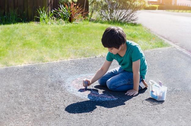 Kid colorare arcobaleno sul marciapiede, bambino disegno arcobaleno con gessetti colorati sul sentiero per conto suo.