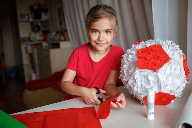 Bambino che fa la pinata con cartone da scatola usata e carta colorata decorazione fai da te alla festa di compleanno