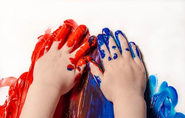 Il bambino disegna con le mani il primo disegno con le vernici concetto di arte e educazione creativa