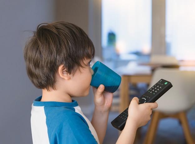 Kid bere soda drink in vetro di plastica e tenendo il telecomando