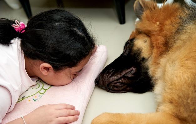 Faccia di bambino sdraiata su cuscino con cane