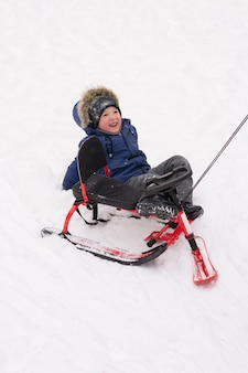 Il bambino è caduto dallo scooter da neve nella neve