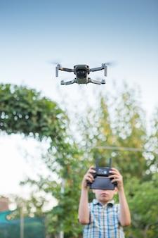 Kid flying drone utilizzando il telecomando del drone