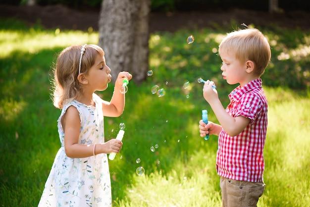 Bambino e amici giocano una bolla nel parco giochi con il tramonto
