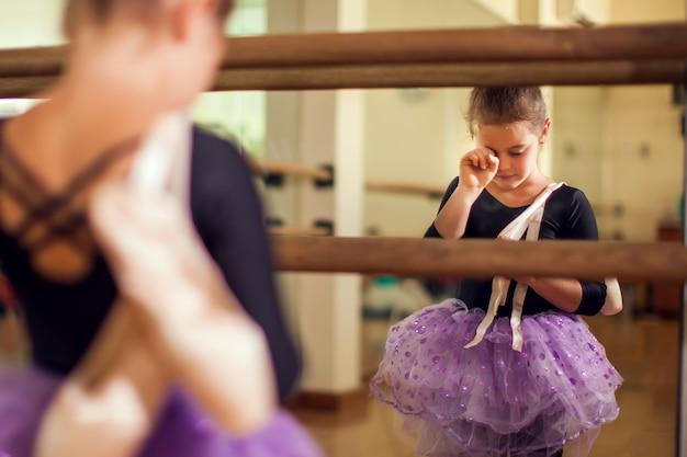 Ragazza del bambino al corso di danza che tiene le scarpe da punta e la colorazione delle lacrime dopo un duro allenamento. bambini e concetto di sport