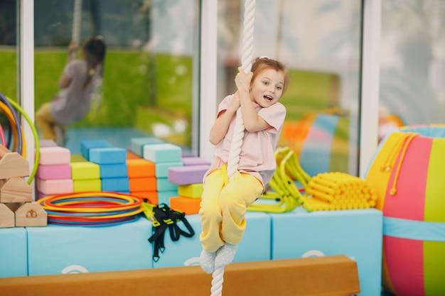 Ragazza del bambino che fa esercizi arrampicata sul filo del rasoio in palestra all'asilo o al concetto di sport e fitness per bambini delle scuole elementari