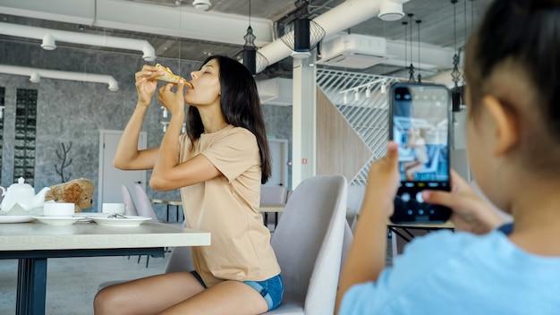 La bambina filma la mamma. una bambina intelligente tiene in mano uno smartphone nero e fa la foto di una madre asiatica bruna che mangia pizza in un ristorante locale vista ravvicinata
