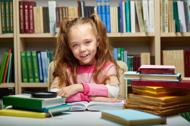 Kid girl si siede con i libri a tavola in biblioteca, bambino in libreria, circondato da libri colorati per la scuola, guarda sorridente della fotocamera
