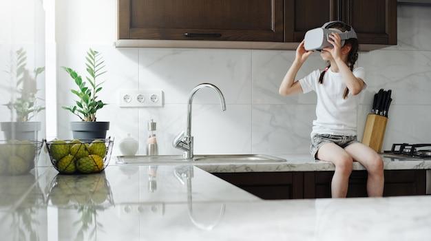 Ragazza del bambino utilizzando occhiali per realtà virtuale a casa