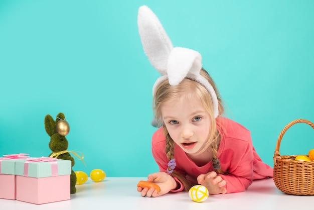 Ragazza del bambino con le uova dipinte di pasqua. la ragazza sorpresa indossa le orecchie da coniglio durante le vacanze di primavera. decorazione festiva, simbolo, tradizione, celebrazione, preparazione.