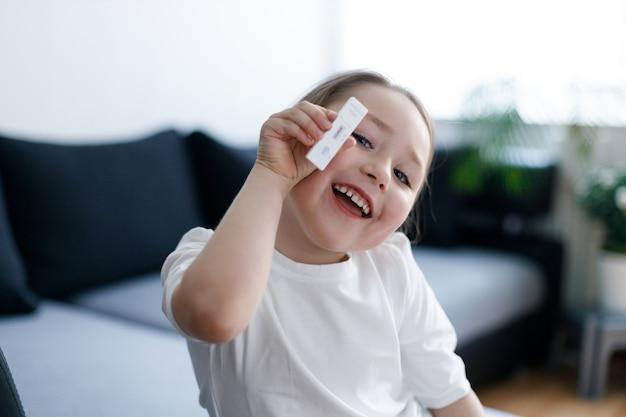 Ragazza del bambino con la striscia reattiva per la malattia da virus anticorpo o sars-cov-2 nelle mani