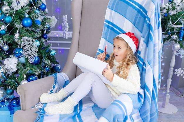 La ragazza del bambino scrive una lettera a babbo natale all'albero di natale, il concetto di nuovo anno e natale