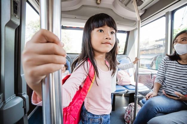 Bambino che va a scuola la mattina con i mezzi pubblici